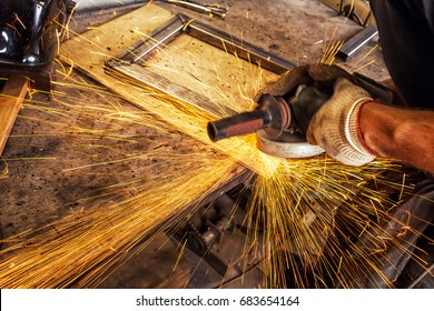 A close-up of a strong man with hardened hands welds a metal welding machine on a wooden table, many sparks fly apart
