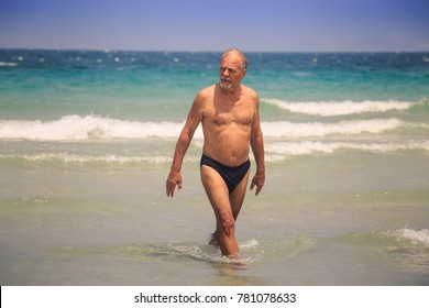 closeup strong tanned bearded old man walks out of azure sea foamy waves against wave surf