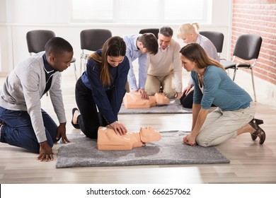 Closeup of Students Practicing CPR Chest Compression On Dummy