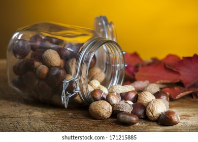 closeup studio photo of fall fruits falling out the glass bowl on wooden table with red leaves on dark yellow background