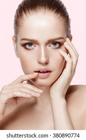 Closeup studio portrait of beautiful model with professional makeup on pink background. Perfect fresh clean skin. Blue eyes. Brunette hair. Not isolated