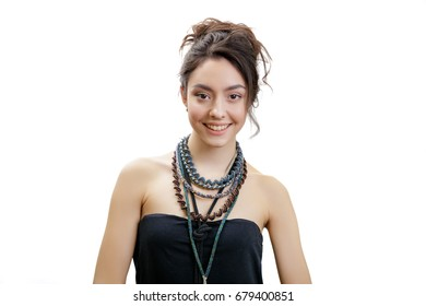 Closeup studio portrait of beautiful smiling young woman. Girl has brown hair bun. Voluminous necklaces are on her neck and black strapless dress. Isolated on white background.