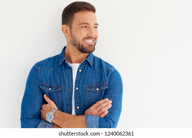 Close-up studio portrait of casual young man standing wiith arms crossed at isolated white background.