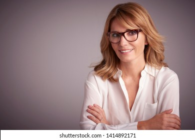 Close-up studio portrait of confident attractive woman sitting at grey background while looking at camera and smiling.