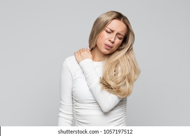 Closeup studio portrait of cute unhealthy young blonde female in white top with pain in her neck and back.Cervical arthritis, osteochondrosis, diseases of the musculoskeletal system concept.