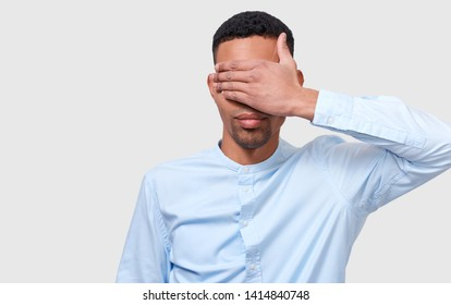 Closeup studio portrait of a handsome African American man cover eyes with hand wearing blue casual shirt isolated on white background. Secrecy businessman blindfolded protection. People and business