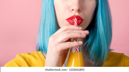 Closeup studio portrait of hipster young woman with red lips and blue dyed hair drinking orange juice from retro bottle with straw. Closeup female mouth and summer cocktail. Trendy pastel background