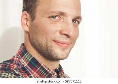 Closeup studio portrait of smiling young adult Caucasian man in colorful casual shirt