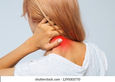 Closeup studio portrait of unhealthy young blonde female in white top with pain in her neck and back, coloured in red. Cervical arthritis, osteochondrosis, diseases of the musculoskeletal system