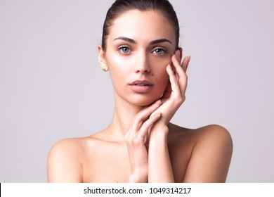 closeup studio portrait of young beautiful brunette woman with hands near her face and clean fresh skin isolated on light grey studio background