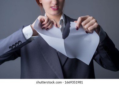 close-up. Studio portrait of a young business woman, with red lipstick, and a gray business jacket, tearing a blank paper, with a grin. On a gray background. Promotional photo