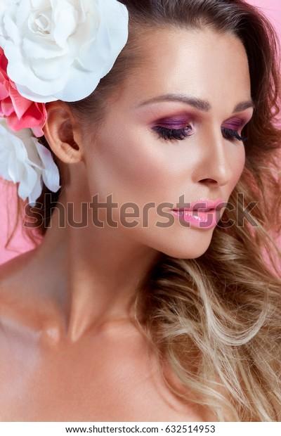 Closeup studio portrait of young caucasian woman in pink makeup