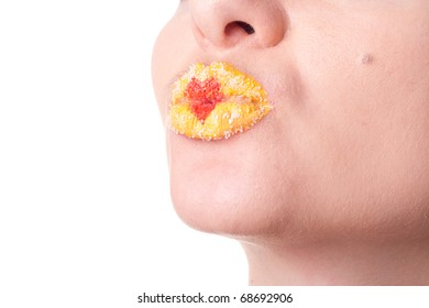 Closeup studio portrait of young female lips with yellow lipstick and red St. Valentine heart