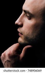 Close-up Studio portrait of young sexy man face hand-touch , holding chin. Beautiful male profile.