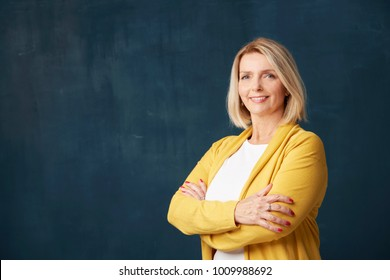 Close-up studio shot of a beautiful mature woman standing with arms crossed at dark bacgkround.