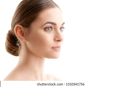 Close-up studio shot of beautiful young woman standing against at isolated white bakcground and looking away.