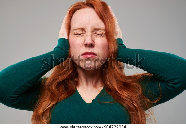 Close-up studio shot of girl with red hair covering ears with hands. Too much noise concept
