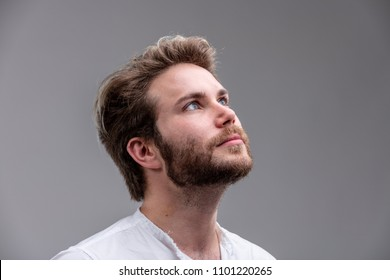 Close-up studio shot portrait of a handsome young man with blond hair and beard looking up while thinking of a new idea for the future