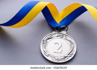 Close-up studio shot of second place silver medal with striped blue and yellow ribbon on gray background