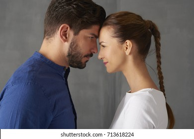 Close-up studio shot of a young affectionate woman and man standing opposite each other. Young couple look at each other's eyes and smile.
