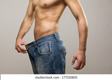 Closeup studio shot of a young Caucasian fit man wearing big jeans after diet. Copy space available. Diet, healthy lifestyle concept.