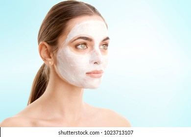 Close-up studio shot of young woman wearing a face mask against at isolated background with copy space.