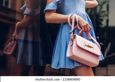 Close-up of stylish female handbag. Fashionable woman holding beautiful accessories outdoors.