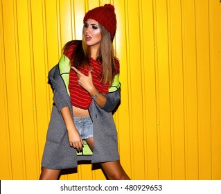 Close-up Stylish night flash fashion portrait of trendy casual young woman in autumn warm outfit,grey jacket,stylish knitted hat,emotional hipster girl,posing over yellow urban wall along,filter,cool