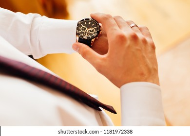 Close-up stylish watch on the groom's hand who looks at the dial