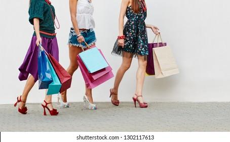 Closeup of stylish women in high heels shoes walking with shopping bags