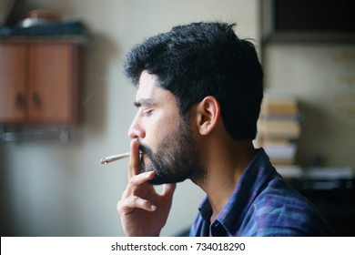 A closeup of a stylish young Indian guy smoking a marijuana joint and blowing the smoke out form his nose and mouth.