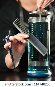 Close-up of a stylist putting a comb into clear glass container of disinfectant full of combs.