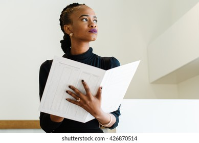 Close-up of successful African or black American business woman holding big white file and thinking