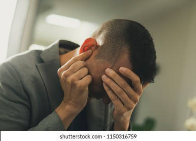 closeup of a suffering caucasian man with one hand in his head and the other hand covering his ear