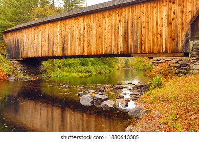 Closeup of Sugar River flowing beneath historic Corbin wooden bridge in Newport, New Hampshire, on a rainy fall day.