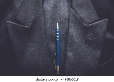 Closeup of a suit pocket with a metallic blue pen on a business coat