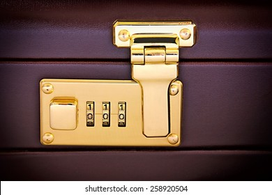 Close-up of suitcase's golden code lock.