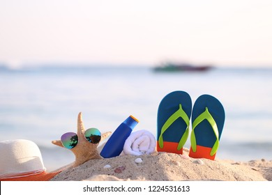Closeup of Summer beach with accessories of blue flip flops, hat, sun protection cream, towel and sunglasses on starfish in tropical beach
