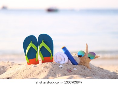 Closeup of Summer beach with accessories of blue flip flops, sun protection cream, towel and sunglasses on starfish in tropical beach
