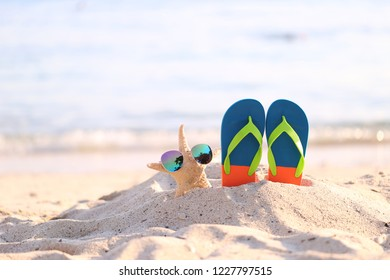 Closeup of Summer beach with blue flip flops and sunglasses on starfish in tropical beach