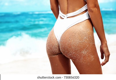 Closeup summer photo of sunbathed sandy woman buttocks posing on crystal sea of tropical beach background. Hands on ass