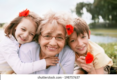 Closeup summer portrait of happy grandmother with grandchildren outdoors