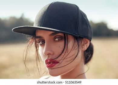 Closeup summer sunny beauty lifestyle fashion portrait of beautiful sexy stylish hipster young woman. Wearing black cap. Professional makeup.