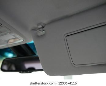 closeup of sun visor with mirror in car.