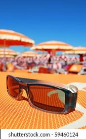 Closeup of sunglasses and beach with orange umbrellas in background, Rimini, Italy
