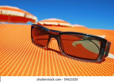 Closeup of sunglasses on orange background and beach with umbrellas in background, Rimini, Italy