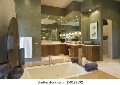 Closeup of sunken bath with cabinets and mirror in background at bathroom in home