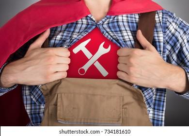 Close-up Of Superhero Handyman Opening Shirt For Showing Worktools Sign