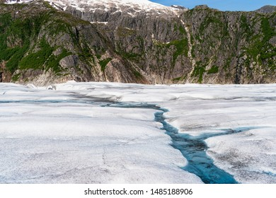 closeup of the surface of the mendenhall glacier near juneau alaska with the canyon wall in the background