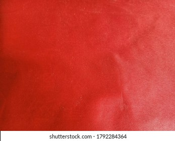 Close-up surface photo of the old red cotton cloth with wrinkles and faded marks. The abstract picture of red cloth with wrinkles for decorative design.